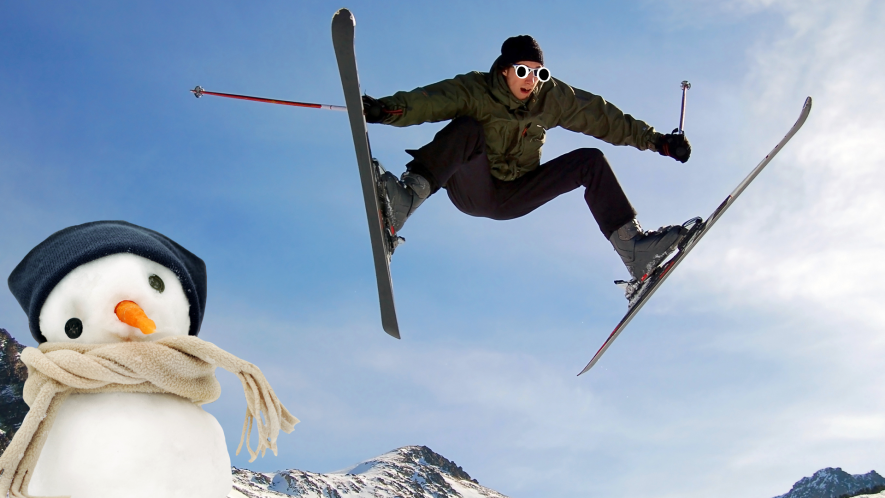 A skier doing a trick over a snowman