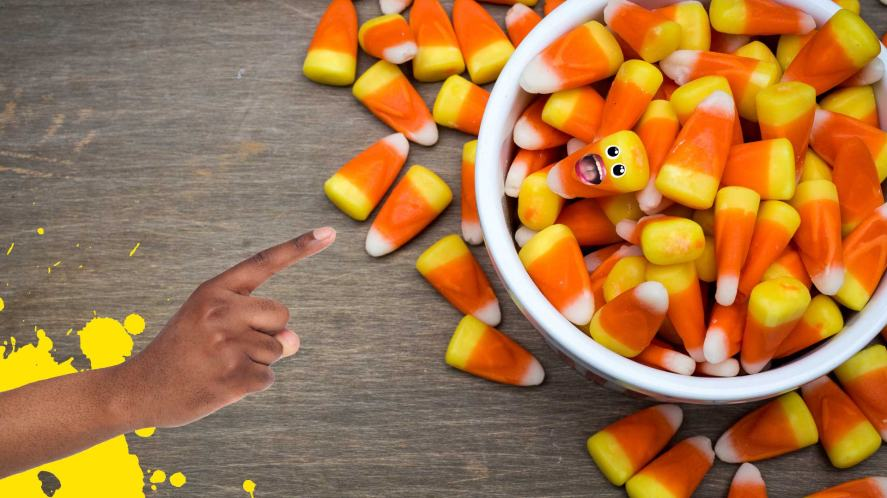 A finger pointing at a bowl of candy corn