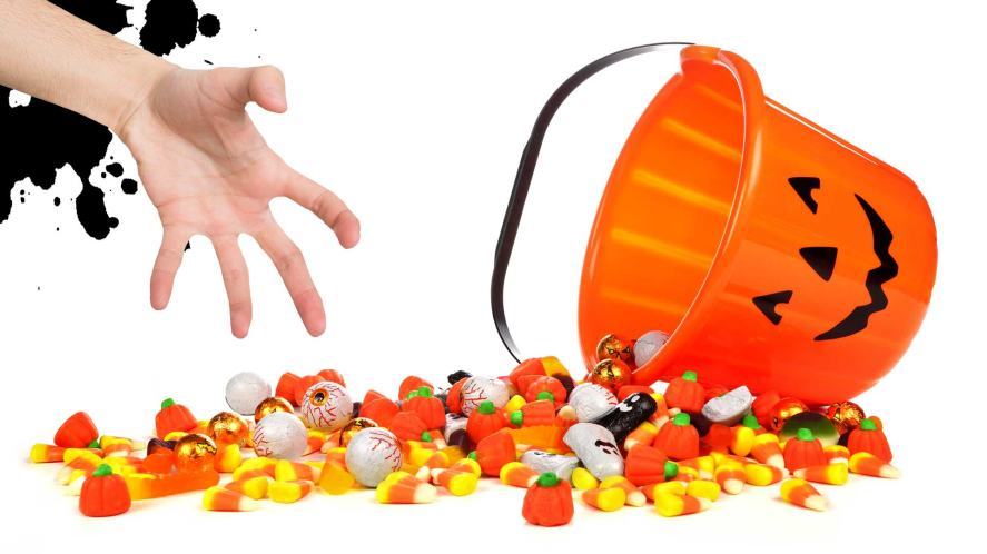 A hand reaching for a bucket of spilled Halloween sweets