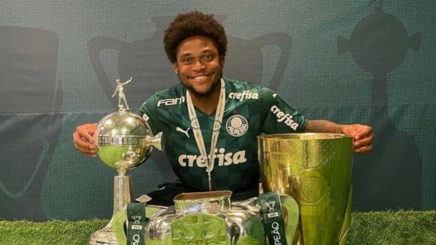 Luiz Adriano poses with several trophies and a medal