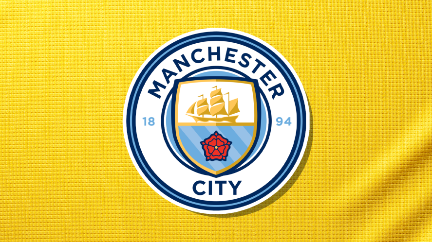 A Manchester City badge on a yellow shirt