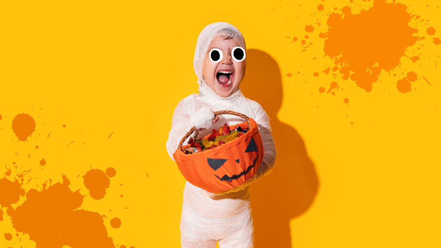 Boy dressed as mummy on orange background with orange splats