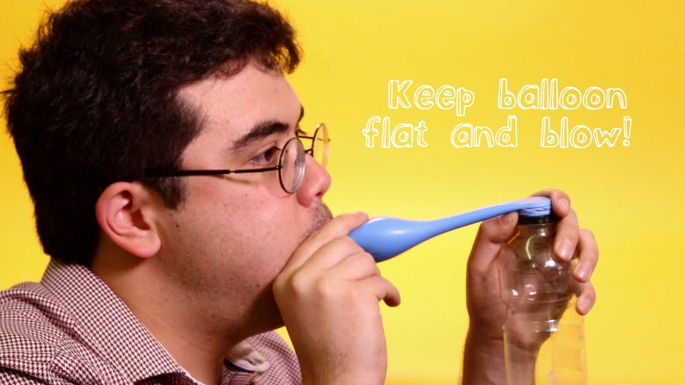Keep the balloon tight by holding the mouth of the bassoon below the top of the bottle. Now blow!