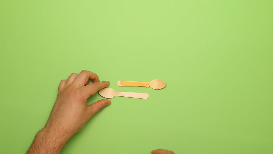 Place the small strip of paper on one of the spoons