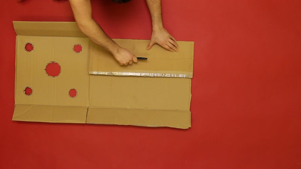 Cut holes in the top half of a sheet of cardboard, and fold and tape the flaps to create guard rails