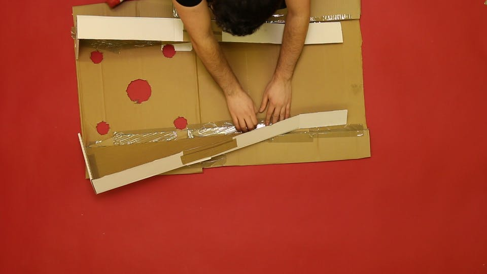 Attach the supports to the bottom of the board, using plenty of tape.