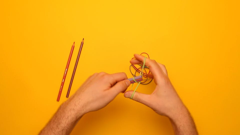 Tie two pencils together at both ends with rubber bands