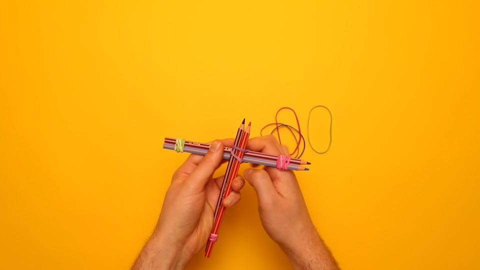 Tie the pencils together in a cross shape with more rubber bands, like this: