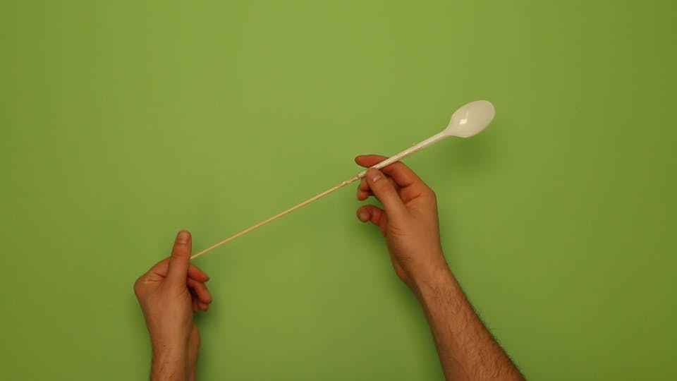 Attach the spoon to a skewer using some sticky tape
