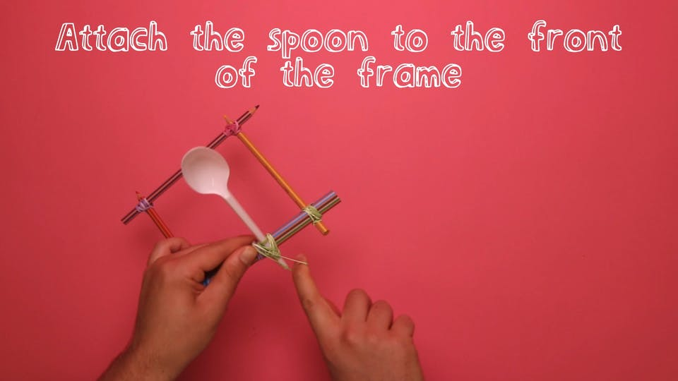 Attach the spoon onto the thick side of the frame with (…you guessed it…) more rubber bands