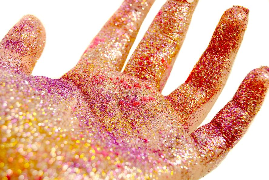 A hand covered in glitter