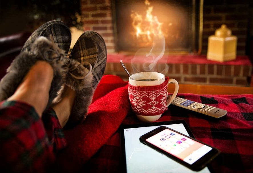 Relaxing by a fire with a hot drink