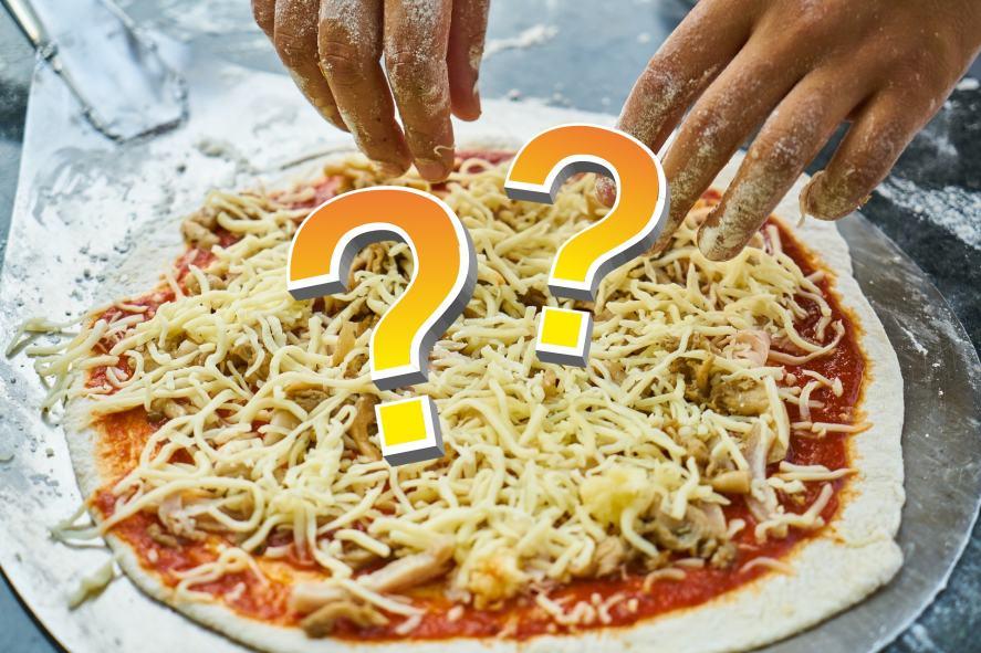 A chef prepares a cheesy pizza