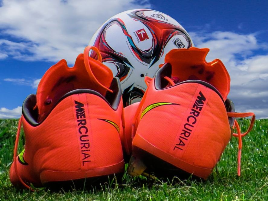 A pair of football boots and a football