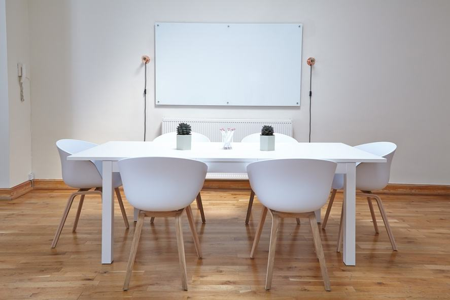 A whiteboard with a desk and chairs arranged in front