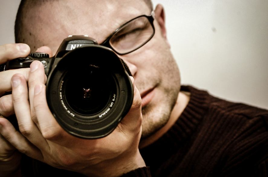 A photographer looking into his camera viewfinder