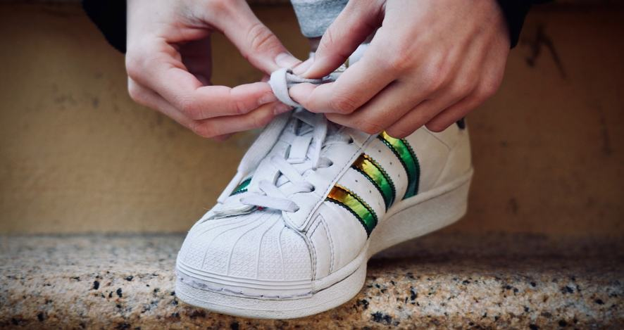 A photo of someone putting their trainers on