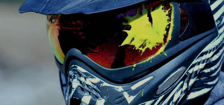 A close-up of a paintballer whose visor is covered in paint