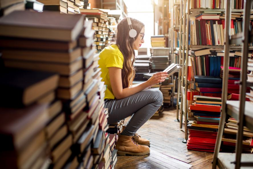 A woman listening to music in a library