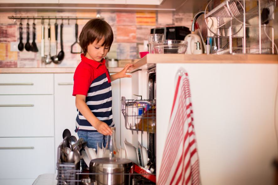 A boy stacking the dishwasher