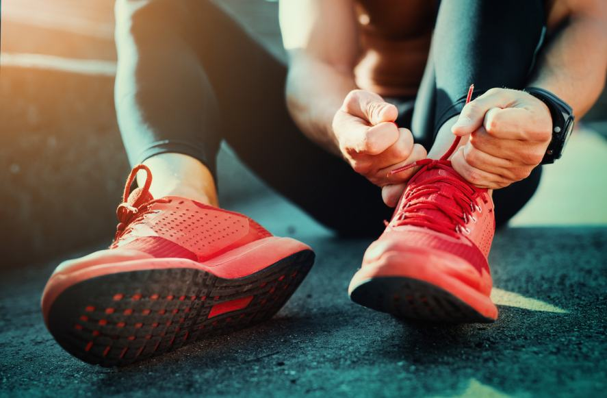 A person laces up their running shoes