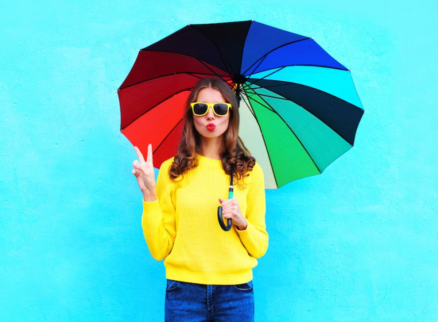 A woman in a bright yellow jumper holding a rainbow umbrella