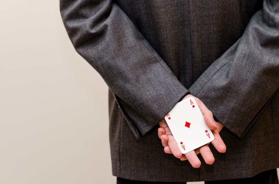 A man with a card up his suit sleeve