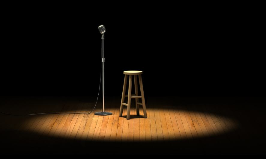 A microphone and stool on an empty stage