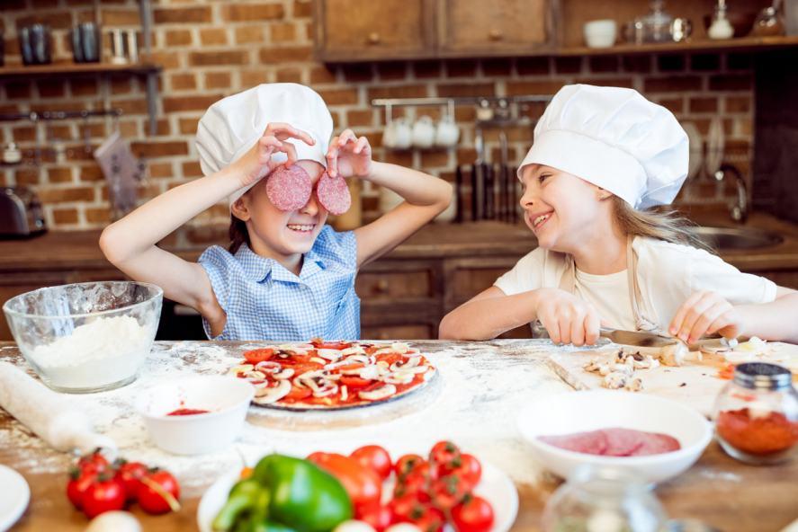 Two kids make a pizza