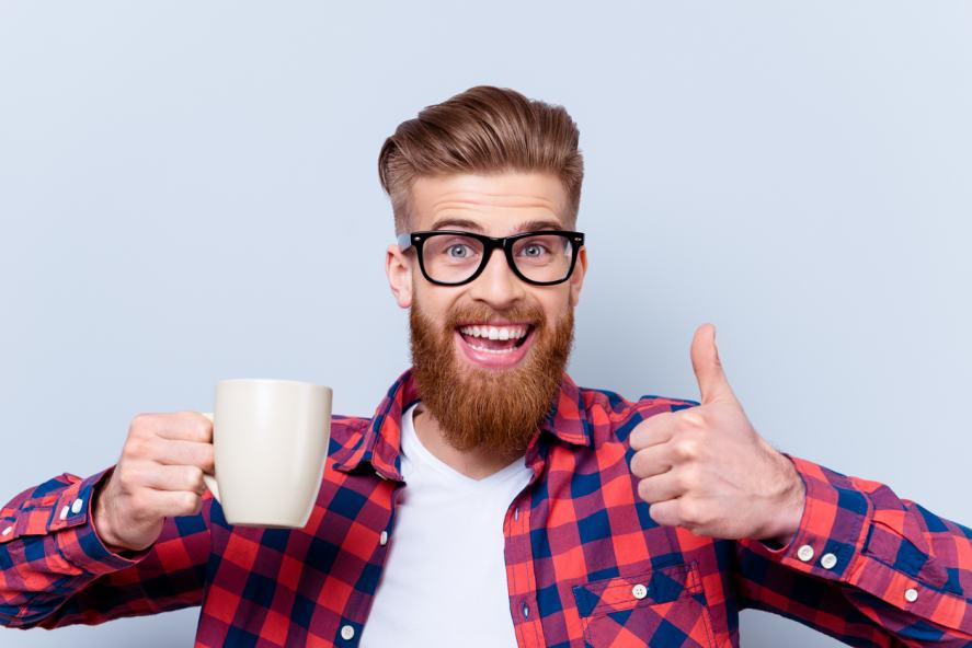A bearded man looking thrilled with a cup of coffee