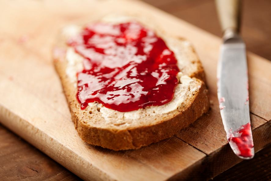 A hot slice of toast smeared with strawberry jam