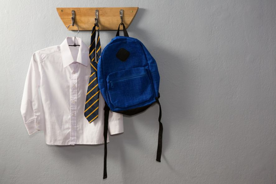 A school uniform and a bag hanging neatly on a hook