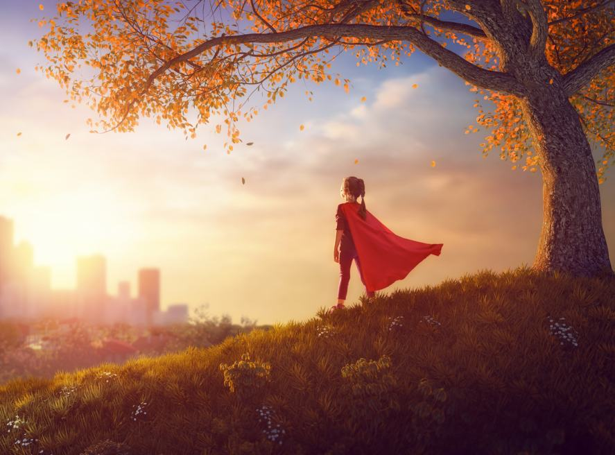 A superhero stands on a park hill