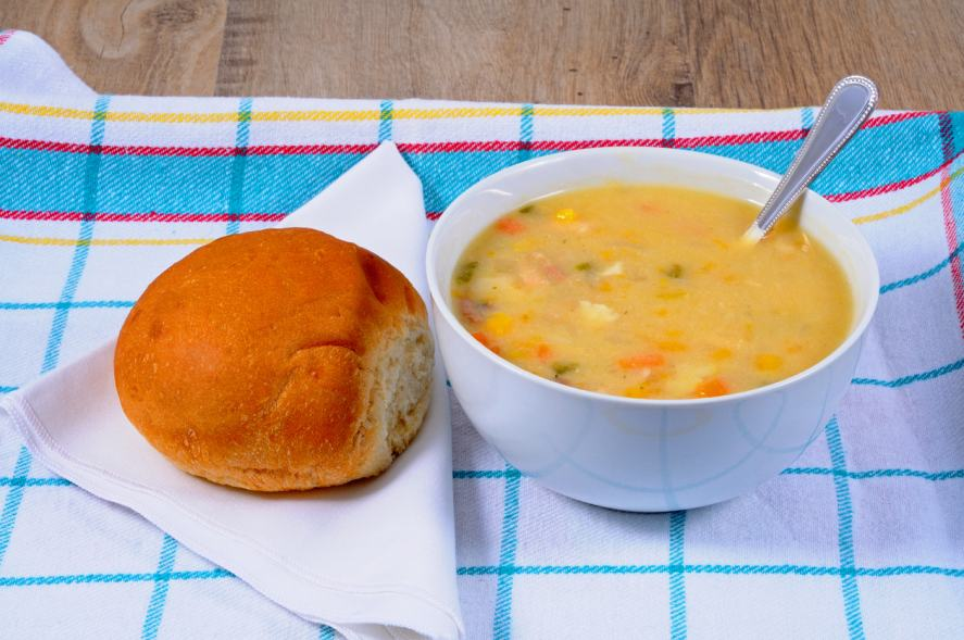 A bowl of soup and a bread roll