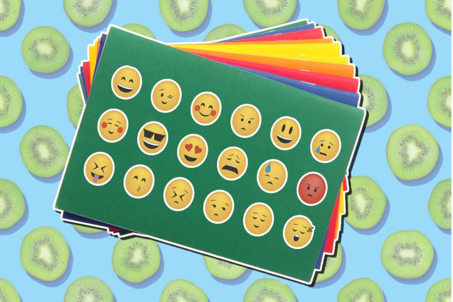 An exercise book covered in emoji stickers