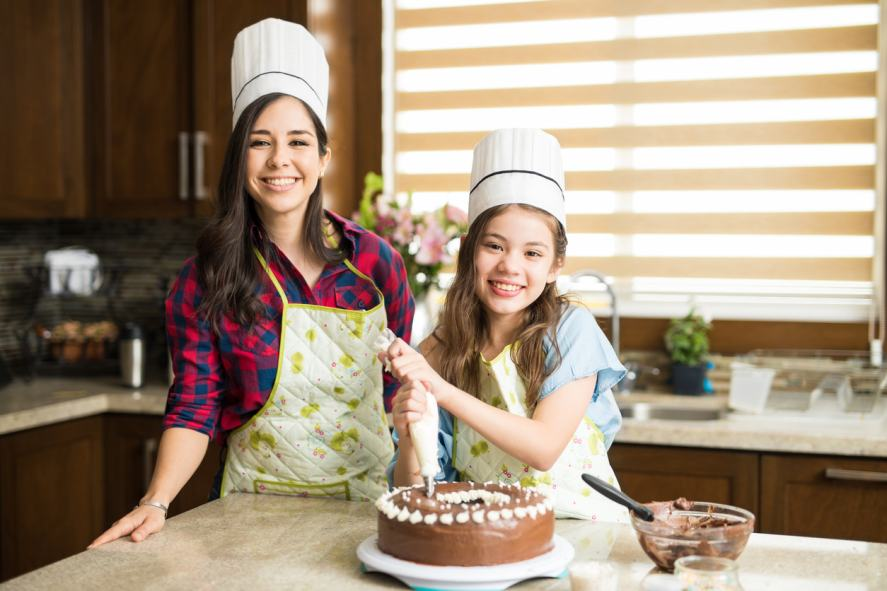 Two bakers icing a cake