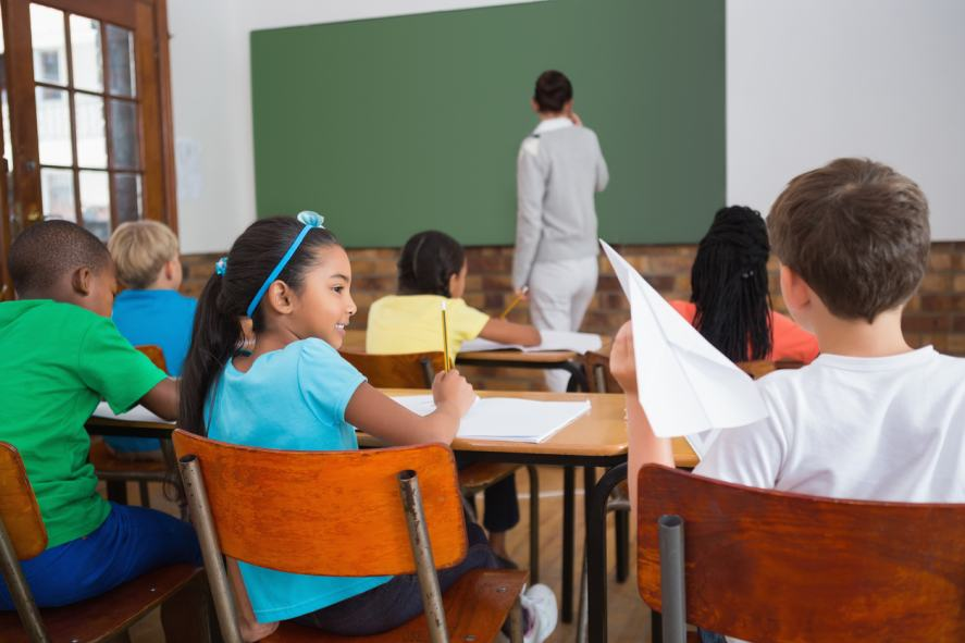 A student about to throw a paper aeroplane at the teacher