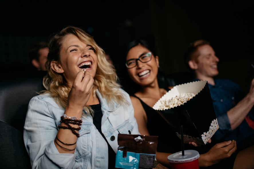 Two friends sharing popcorn at the cinema