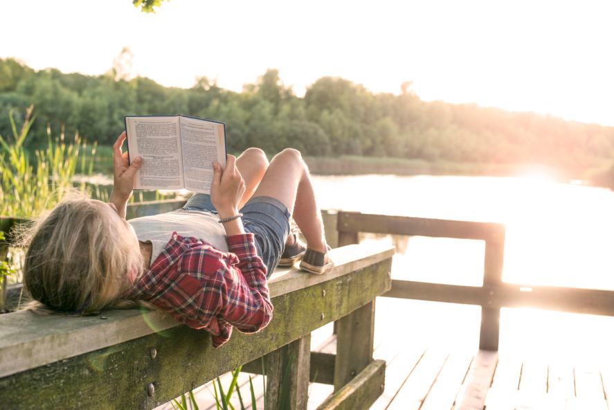 A child relaxing by the lake with a good book
