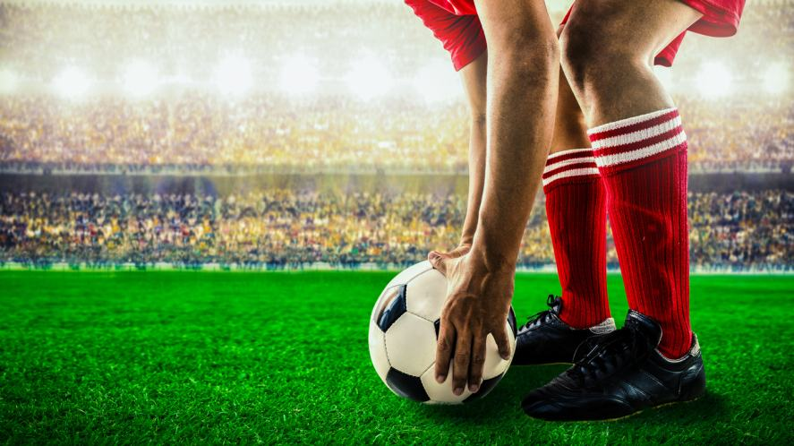 A football player prepares to take a free kick