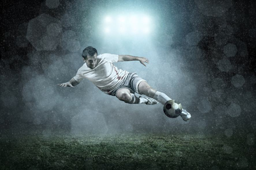 A brilliant football player shooting at the goal