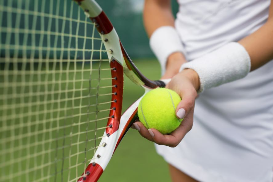A woman standing with tennis racquet