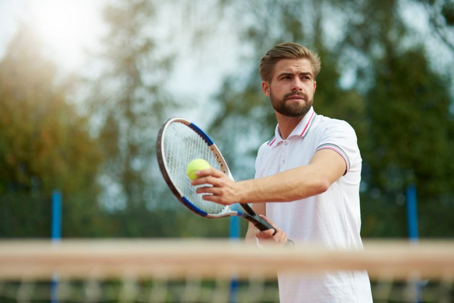A tennis player prepares to serve the ball