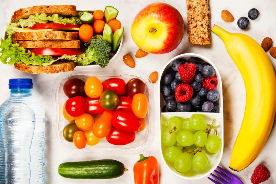 Healthy lunch box with sandwich and fresh vegetables, bottle of water and fruit