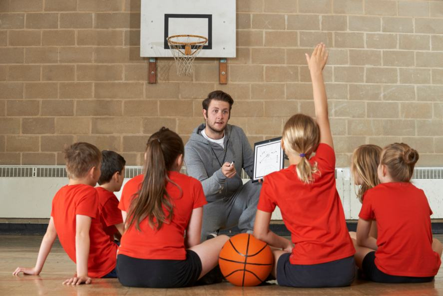 Teacher giving talk to school team