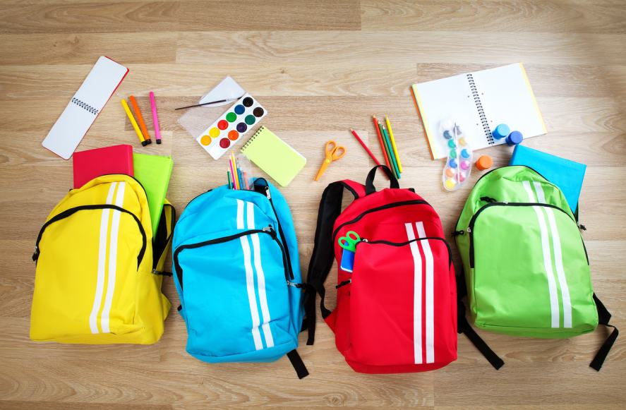 Colourful schoolbags on a wooden floor