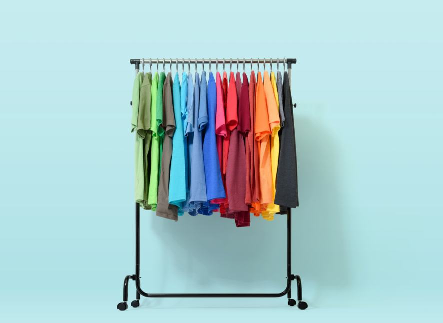 Mobile rack with color clothes on light blue background