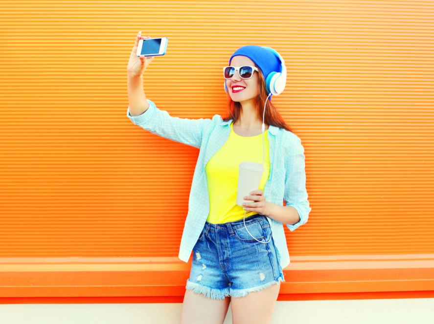 A woman takes a selfie against an orange background