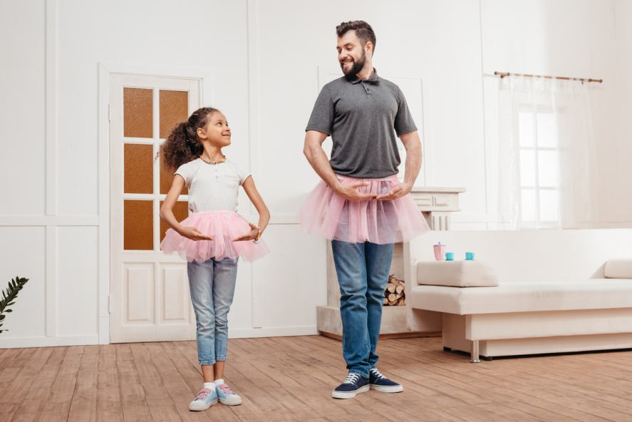 A family in pink tutu tulle skirts dance at home