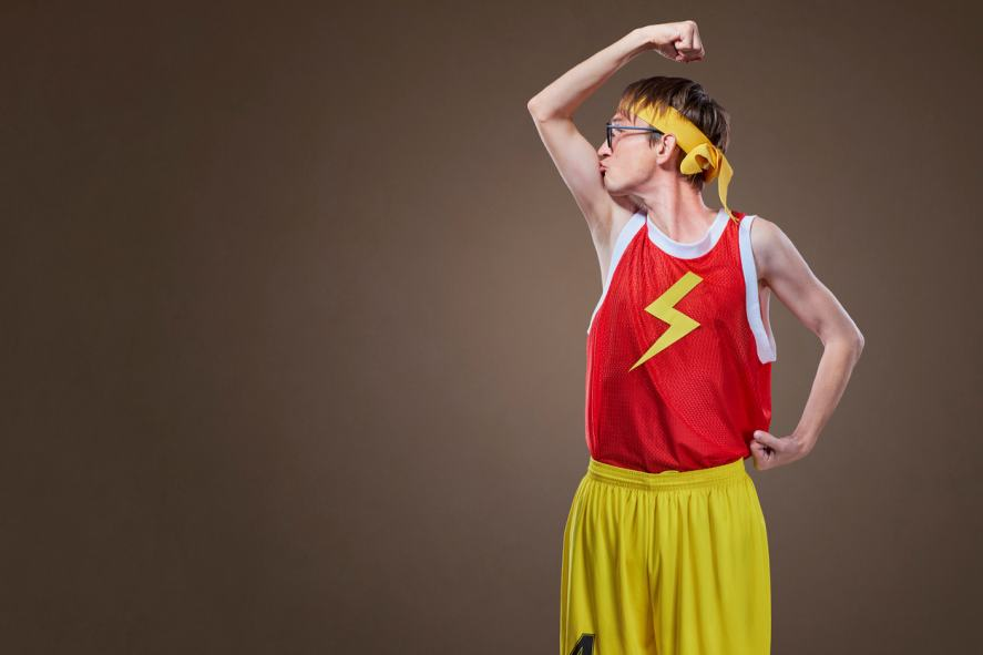 A thin guy in sports clothes kisses his arm muscle
